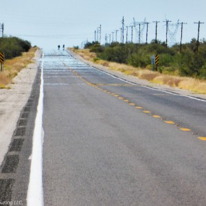 A long road with two bicyclists in the distance