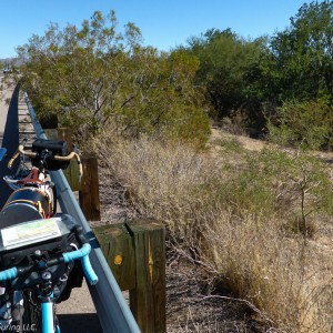 Two bicycles lean agains a guardrail on the side of a highway in Texas