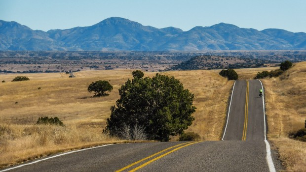A bicycle tourist rides away among rolling hills