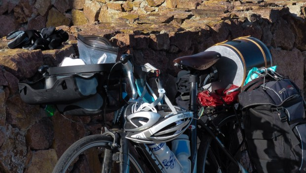 a bicycle loaded with gear leans against a rock wall