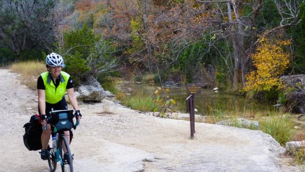 A bicyclist rides along a dirt path.