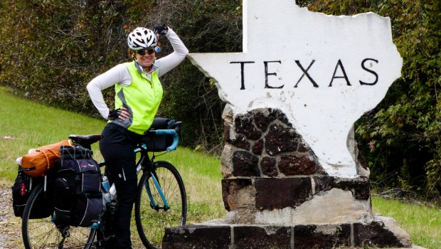 A cyclist leans against a welcome to Texas sign