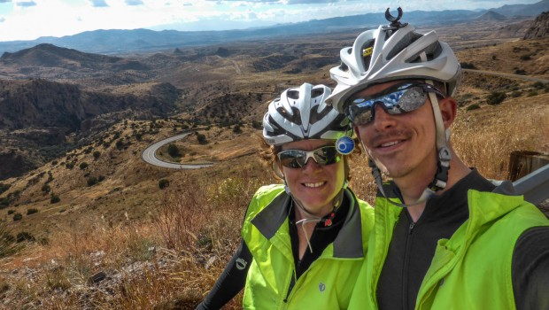 Two cyclists with a winding road behind them.