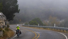 A bicyclist rides through the fog on a curvy road.