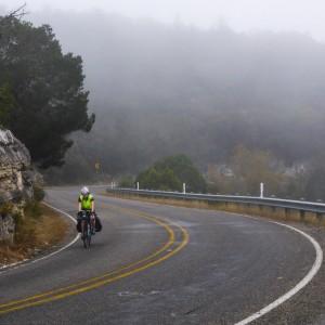 A bicyclist rides through the fog on a curvy road.
