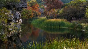 A smooth surface on a pond with fall foliage in the background
