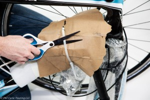 Hand with scissors cutting zip tie holding packing material on the bicycle.