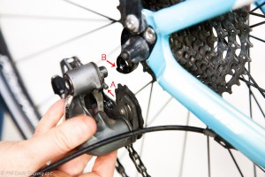 Hand holding rear derailleur near bicycle frame before attaching it.