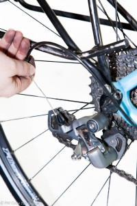 Hand threading cable through rear derailleur on a bicycle