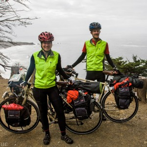 Two bicyclists and their bicycles and gear overlooking the ocean
