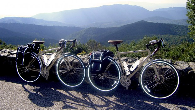 Two loaded touring bicycles leaning against a wall with mountains in the background