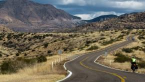 Bicyle tourist rides up a steep hill on AZ 78 in Arizona.