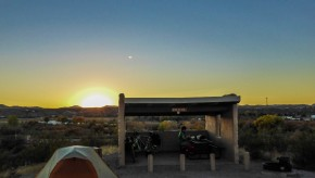 The sun sets behind a tent and picnic structure.