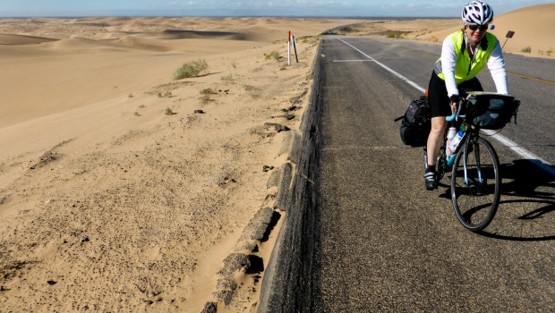 A bicycle tourist rides on the shoulder of a road with sand dunes on either side.