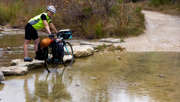 A bicyclist uses stepping stones to cross a stream while pushing her bicycle