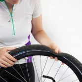 Upside down bicycle with flat tire being held by Pam