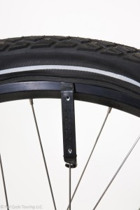 Prying the tire over the rim by inserting a tire lever, then use the hook end to attach to spoke, freeing up your hands for a second tire lever.