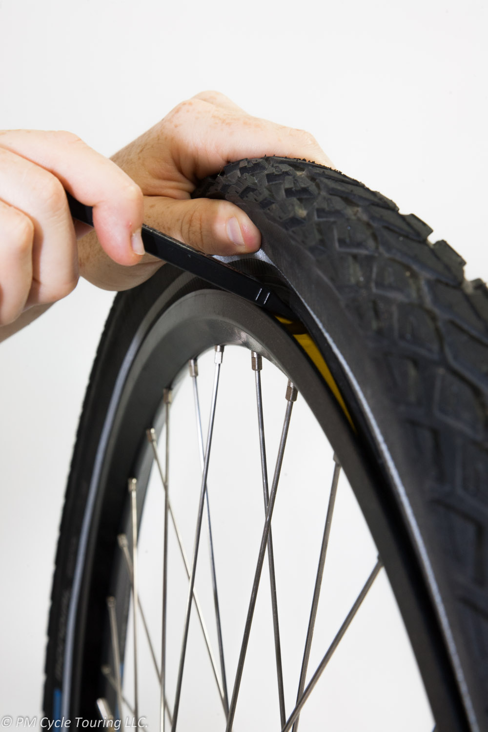 Prying the tire over the rim by inserting a tire lever.