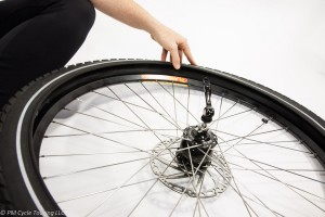 Bicycle wheel on the ground with one side of the tire reomove from the wheel