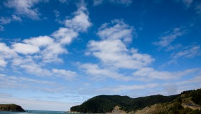 A view of deep blue sky with white fluffy clouds over a hill with a road winding down on the right side. The ocean is on the left with waves crashing ashore.