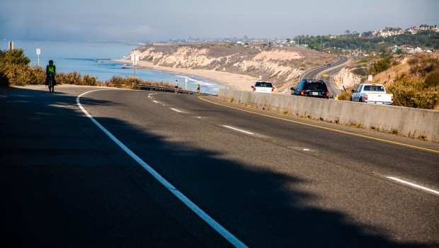A bicycle rider climbing a hill near the ocean in La Jolla, California