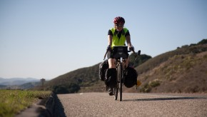 A bicycle rider with a loaded touring bicycle rides along the shoulder of a road.