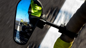 A clamp on bicycle mirror shows a cyclist behind.