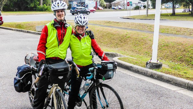 Two bicycle tourist with fully loaded touring bicycles pose at the end of a long journey