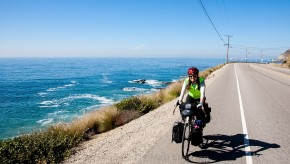 A bicycle rider on a fully loaded touring bicycle rides on the shoulder near the ocean