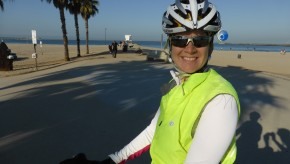 A cyclist faces the camera and smiles with a bike path in the background.