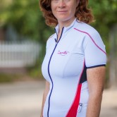 A woman wearing a short sleeve, white, full zippered cycling jersey