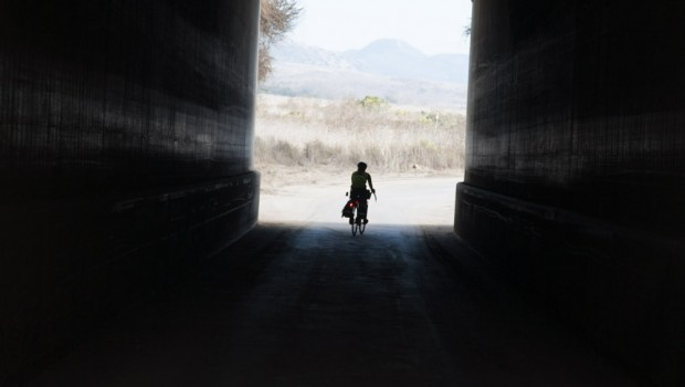 A bicycle tourist rides through a tunnel