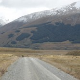 A cyclist rides a gravel road with snow capped mountains surrounding