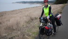 A woman on a touring bicycle stopped near the Pacific Ocean