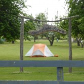 a tent set up in a field, framed by a farm sign