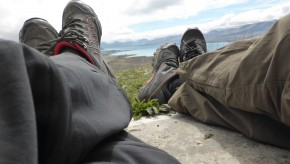 Lake Tekapo in the distance, two sets of legs and shoes in the foreground