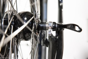 A close-up of stainless steel dropouts on a front wheel