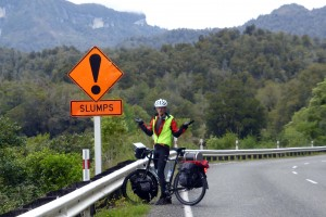 "A bicyclist stands next to a road sign which reads ""slumps"""