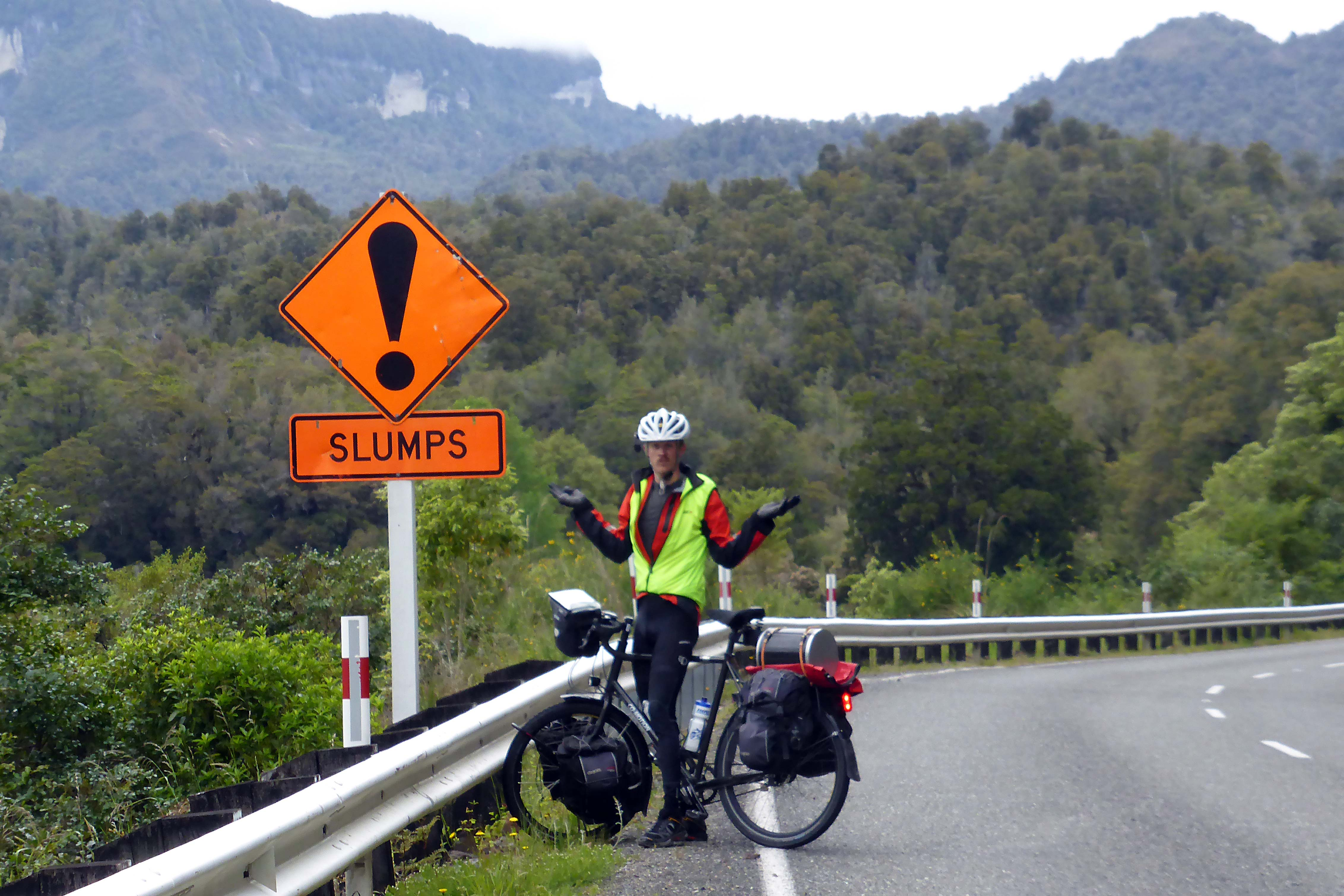 """A bicyclist stands next to a road sign which reads """"slumps"""""""