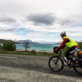 A woman on a fully loaded touring bicycle rides in front of Lake Tekapo, New Zealand